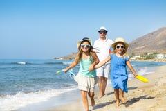 Szczęśliwa młoda rodzina ma zabawa bieg na plaży przy zmierzchem rodzina obraz royalty free