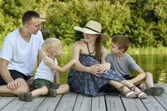 Szczęśliwa młoda rodzina, ojciec matka i dwa małego syna, siedzimy na rzecznym molu zdjęcia royalty free