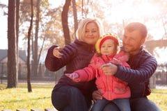 Szczęśliwa Młoda rodzina w parku Robi Wskazywać gest Wpólnie zdjęcia stock