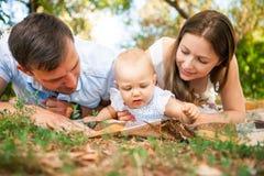 Szczęśliwa młoda rodzina wydaje czas plenerowego na letnim dniu, pinkin Fotografia Royalty Free