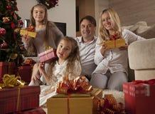 Szczęśliwa młoda rodzina z Bożenarodzeniowymi prezentami Obraz Stock
