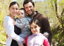 Szczęśliwa młoda rodzina z córkami outdoors Fotografia Royalty Free