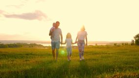 Szczęśliwa młoda rodzina z dwa dziećmi biega na lata polu Zdrowa matka, ojciec i małe dzieci cieszy się naturę, zbiory