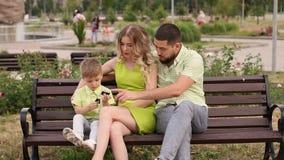 Szczęśliwa młoda rodzina z jego synem odpoczywa w parku w lecie na ławce zbiory wideo