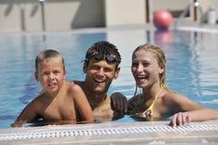 Szczęśliwa młoda rodzina zabawę na dopłynięcia basenie Zdjęcia Stock