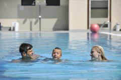 Szczęśliwa młoda rodzina zabawę na dopłynięcia basenie Fotografia Royalty Free