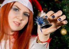 Szczęśliwa młoda rudzielec kobieta jest ubranym Santa bożych narodzeń mienia kapeluszowego dzwon zdjęcia royalty free
