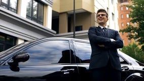 Szczęśliwa młoda samiec stoi bezczynnie nowego luksusowego samochód, urzędnik dostaje promocję zdjęcie stock