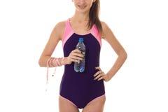 Szczęśliwa młoda seksowna brunetka sportów kobieta w ciała swimsuit pozuje z miarą taśmy i butelka z wodą odizolowywającą na biel Zdjęcia Royalty Free