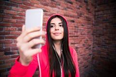 Szczęśliwa młoda sportive kobieta patrzeje na smartphone Zdjęcie Royalty Free