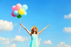 Szczęśliwa młoda uśmiechnięta kobieta z lotniczy kolorowi balony cieszy się letniego dzień nad niebieskiego nieba tłem zdjęcie royalty free