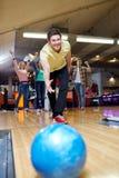 Szczęśliwa młodego człowieka miotania piłka w kręgle klubie Zdjęcia Royalty Free