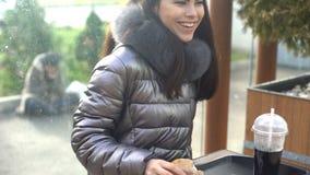 Szczęśliwa młodej kobiety mienia kanapki kawiarnia, bezdomny siedzący outside, społeczeństwo zdjęcie royalty free