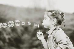 Szczęśliwa mała ładna dziewczyna plenerowa w parkowym dmuchaniu gulgocze zdjęcia stock