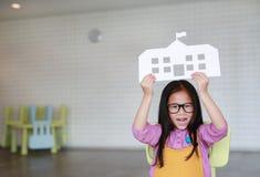 Szczęśliwa mała Azjatycka dziecko dziewczyna trzyma w górę papier szkoły obsiadania na dzieciaka krześle w sali lekcyjnej z patrz zdjęcia stock