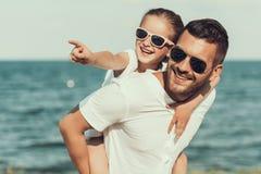 Szczęśliwa mała córka w okularach przeciwsłonecznych siedzi na ojcach z powrotem zdjęcie royalty free