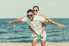 Szczęśliwa mała córka w okularach przeciwsłonecznych siedzi na ojcach z powrotem obrazy stock