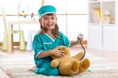 Szczęśliwa mała doktorska dziewczyna egzamininuje misia w pepiniera pokoju w domu obraz stock
