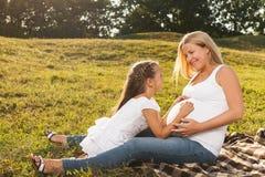 Szczęśliwa mała dziewczynka ściska jej matki ciężarnego brzucha Obraz Stock