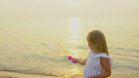 Szczęśliwa mała dziewczynka Bawić się dowcipów Mydlanych bąble plenerowych na plaży podczas pięknego zmierzchu szczęśliwego urlop zbiory wideo