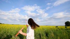 Szczęśliwa mała dziewczynka bawić się wśród mydlanych bąbli na zielonej łące w lecie zbiory wideo