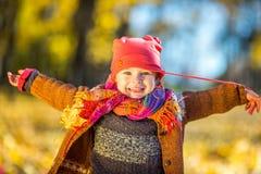 Szczęśliwa mała dziewczynka bawić się w jesień parku Obrazy Stock