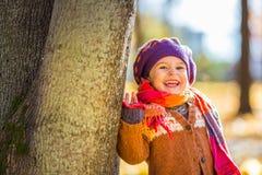 Szczęśliwa mała dziewczynka bawić się w jesień parku Fotografia Royalty Free