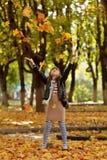 Szczęśliwa mała dziewczynka bawić się z jesieni ulistnieniem w parku Obraz Royalty Free