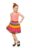 Szczęśliwa mała dziewczynka folował długość w kolorowej spódnicie, odizolowywającej na białym tle Fotografia Royalty Free