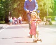Szczęśliwa mała dziewczynka i ojciec na hulajnoga w zdjęcie royalty free