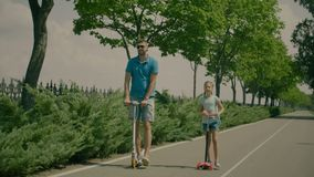 Szczęśliwa mała dziewczynka i tata na hulajnoga w lato parku zbiory wideo