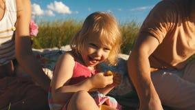 Szczęśliwa mała dziewczynka je ananasa i ono uśmiecha się przy kamerą zbiory