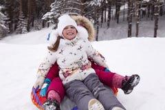 Szczęśliwa mała dziewczynka krzyczy z zachwytem, stacza się z śnieżnym wzgórzem Fotografia Stock