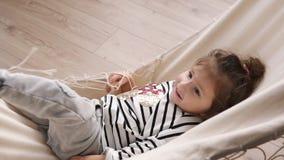 Szczęśliwa mała dziewczynka ma zabawę, kłama w hamaku i macha ona indoors, nogi dziecko się uśmiecha zbiory wideo