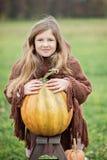 Szczęśliwa mała dziewczynka na dyniowej łacie na zimnym jesień dniu z mnóstwo baniami dla Halloween lub dziękczynienia, obraz royalty free