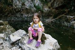 Szczęśliwa mała dziewczynka odpoczywa na dużej skale małym stawem obrazy stock