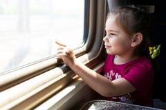 Szczęśliwa mała dziewczynka podróżuje pociągiem fotografia royalty free