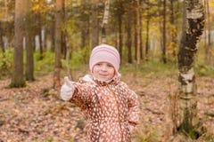 Szczęśliwa mała dziewczynka pokazuje aprobaty w słonecznym dniu na jesieni tle Złoci jesieni drzewa, jezioro i Jesień krajobraz obrazy royalty free