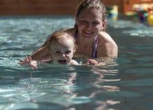 Szczęśliwa mała dziewczynka przy pływacką lekcją z matką Obrazy Stock