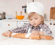 Szczęśliwa mała dziewczynka robi pizzy ciastu fotografia stock