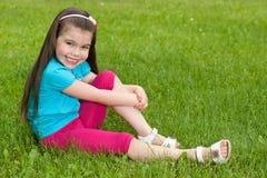Szczęśliwa mała dziewczynka siedzi na trawie Obrazy Stock