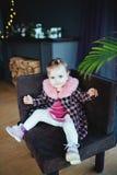 Szczęśliwa mała dziewczynka siedzi w krześle Obrazy Stock