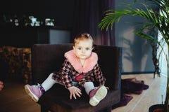 Szczęśliwa mała dziewczynka siedzi w krześle Obraz Stock