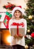 Szczęśliwa mała dziewczynka trzyma dużego Bożenarodzeniowego prezenta pudełko Fotografia Royalty Free