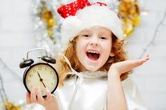 Szczęśliwa mała dziewczynka trzyma zegar w jego w Santa kapeluszu ręki Chr Obraz Stock
