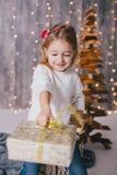 Szczęśliwa mała dziewczynka w białym pulowerze i niebieskich dżinsach pozuje blisko choinki Zdjęcie Stock