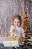 Szczęśliwa mała dziewczynka w białym pulowerze i niebieskich dżinsach pozuje blisko choinki Obraz Royalty Free