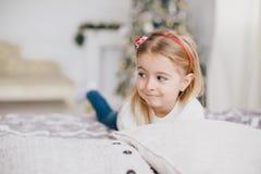 Szczęśliwa mała dziewczynka w białym pulowerze i niebieskich dżinsach pozuje blisko choinki Zdjęcia Royalty Free