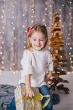 Szczęśliwa mała dziewczynka w białym pulowerze i niebieskich dżinsach pozuje blisko choinki Fotografia Royalty Free