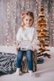 Szczęśliwa mała dziewczynka w białym pulowerze i niebieskich dżinsach pozuje blisko choinki Obraz Stock